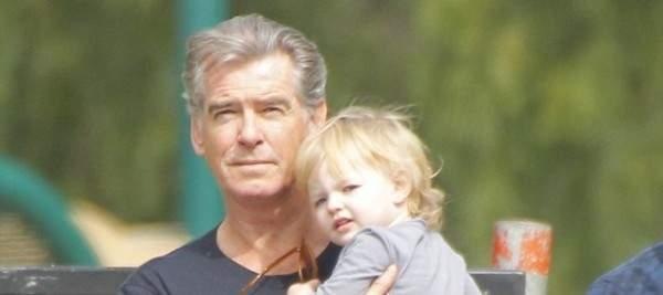 بيرس بروسنان يحمل حفيدته خلال نزهة عائلية